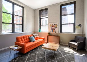 living room with orange couch and grey chair